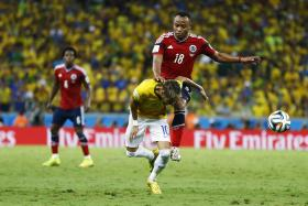 Brazil's Neymar (bottom) is fouled by Colombia's Camilo Zuniga during their 2014 World Cup quarter-finals at the Castelao arena in Fortaleza July 4, 2014. Photo: Reuters