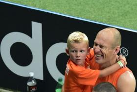 Arjen Robben with carries his son and celebrates after Holland's World Cup victory over Costa Rica.