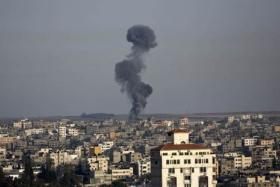 Smoke billows from buildings following an Israeli air strike in Gaza City on July 12, 2014.
