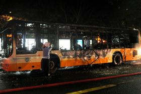 Investigators looking through a bus which had been set on fire on Tuesday by a man in Guangzhou, in southern China's Guangdong province. The blaze killed two people and injured 32 others.