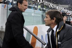 Juventus coach Antonio Conte (right) shakes hands with AC Milan coach Massimiliano Allegri during their Serie A football match on Oct 6, 2013.