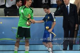 Lionel Messi (left) holds his Golden Ball trophy for the best player of the tournament as they shake hands after Germany won the 2014 FIFA World Cup final football match between Germany and Argentina 1-0 following extra-time at the Maracana Stadium.