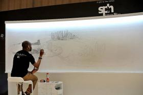 LIVE DRAWING: Stephen Wiltshire drawing Singapore's cityscape from memory on the first day of the live drawing exhibition See The Big Picture at Paragon yesterday. He will be there until Sunday.