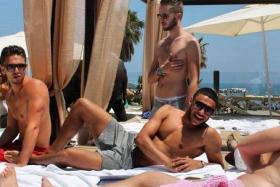 Alex Oxlade-Chamberlain relaxes on Sala Beach in Malaga, Spain with a group of friends.