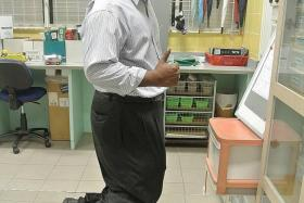 CREATIVE: Mr Mohamed Ashiq Mohamed Elias (above) demonstrating the levitation trick that he uses to get students interested in his physics lesson.