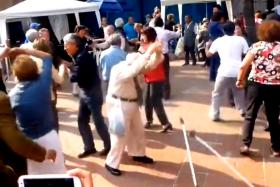 An elderly man throwing his crutches aside before busting out some energetic moves.