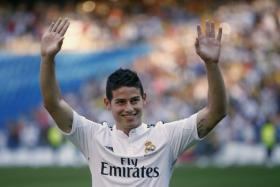 Colombia's soccer player James Rodriguez waves to the fans during his presentation at the Santiago Bernabeu stadium in Madrid, July 22, 2014.
