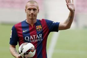 arcelona's newly signed French soccer player Jeremy Mathieu waves while wearing his new jersey during his presentation at Camp Nou stadium, in Barcelona July 24, 2014.