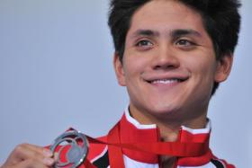 Silver medallist Singapore's Joseph Schooling poses on the podium during the Men's 100m Butterfly medal ceremony at the Tollcross International Swimming Centre during the 2014 Commonwealth Games in Glasgow on July 28, 2014.