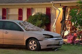 Police say a man purposely crashed a car, seen here, into a Cedar Hill home, trapping his wife in the rubble inside.