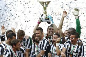 Juventus' captain and goalkeeper Gianluigi Buffon holding the trophy as he celebrates with teammates after winning the Serie A championship at the Juventus stadium in Turin May 18, 2014.
