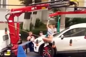 A Russian woman was caught on camera giving an impromptu pole dance to keep her car from being towed.