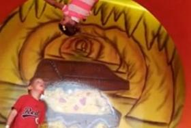 A three-year-old girl hangs upside down after she, not knowingly, gripped tightly onto the side of a spinning barrel ride as she spun 360 degrees before sliding off about 7 seconds later as her feet got closer to the ground.