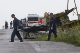 Members of the Ukrainian Emergencies Ministry gather and place bodies at the crash site of Malaysia Airlines Flight MH17, near the village of Hrabove, Donetsk region.