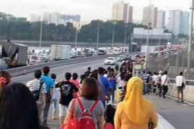 JAMMED UP: (Above) Thousands of commuters had to walk across the Causeway just to get to work in Singapore.