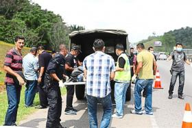 Police removing the remains of a man. His body was found in pieces in plastic bags along an expressway in Malaysia.