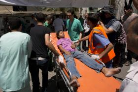 A Palestinian girl, wounded following an Israeli military strike, arrives at the hospital in Rafah in the southern Gaza Strip.