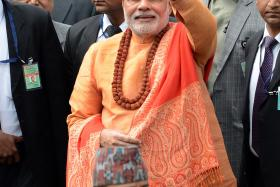 Indian Prime Minister Narendra Modi waves to well-wishers as he leaves Pashupatinath Temple in Kathmandu on Monday.
