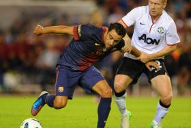 Barcelona's Xavi Hernandez tussles with Manchester United midfielder Paul Scholes during a pre-season friendly in 2012.