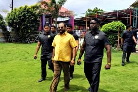 Mr Pankaj Parakh wearing a shirt made of gold as he walks with his bodyguards to attend his birthday celebrations in Yeola, in the western Indian state of Maharashtra on Aug 8.