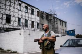 A rebel gunmen patrols a yard of a high-security prison after a shelling in Donetsk on August 11, 2014. Over 100 inmates broke out of jail when shells rained down on the prison.