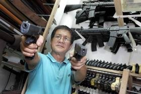 THE REAL DEAL: The real Glock G19 pistol is in Mr Jimmy Low's right hand.