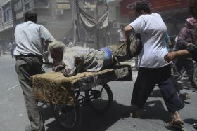 Residents carrying an injured man on a cart, wounded by what activists claim was a car explosion, in central Douma, near the Syrian capital Damascus.