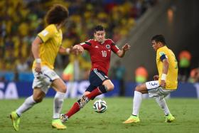 Colombia's James Rodriguez (C) vies with Brazil's Thiago Silva during the quarter-final football match between Brazil and Colombia during the 2014 FIFA World Cup on July 4, 2014.