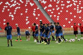 NEW HOME: The Singapore players and national assistant coaches Fandi Ahmad (right) and Aide Iskandar (second from right) getting a feel of the National Stadium pitch.