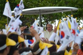 South Korean flags are waved as Pope Francis (C) meets with worshippers after arriving in Kkottongnae, around 80 km south of Seoul, on Aug 16, 2014.