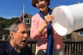 Former US president George W. Bush has a bucket of ice water dumped on him by wife Laura to raise awareness over ALS.