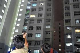 BURNT: Some onlookers pointing out the unit where the fire broke out.