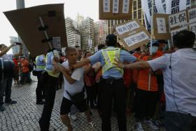 """Workers from Macau's six major casinos, led by union """"Forefront of Macau Gaming"""", clash with police during a protest march in Macau August 25, 2014."""