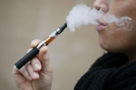 A person smoking an e-cigarette in Paris.