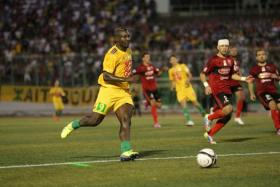 JS Kabylie's Cameroonian striker Albert Ebosse (C) passes the ball during his team's match with USM Alger in the city of Tizi-Ouzou, in the mainly Berber region of Kabylie east of the capital, on August 23, 2014.
