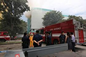 AFTER THE BLAST: Firefighters and police officers outside the Four Star building.