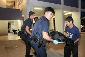 GRISLY FIND: Policemen carrying the body believed to be that of Bukit Panjang resident Lee Ming Quan.