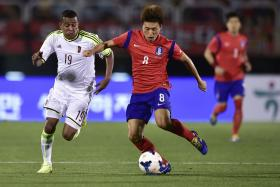 Edjar Jimenez (left) of Venezuela battles for the ball with Lee Myoung Joo  during their friendly on Friday.