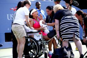 Peng Shuai of China grimacing as she is placed in a wheelchair after dropping to the court in pain during the semi-final match against Caroline Wozniacki of Denmark at the 2014 US Open tennis tournament in New York on Sept 5.