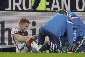 German midfielder Marco Reus receives treatment on the pitch after sustaining an ankle injury against Scotland.