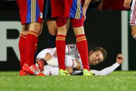 Midfielder Aaron Ramsey lies injured on the Estadio Nacional pitch during  Wales' Euro 2016 qualifier against Andorra.