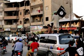 File photo of people waving the flag of the Islamic State of Iraq and Syria as they drive around Raqqa, Syria.