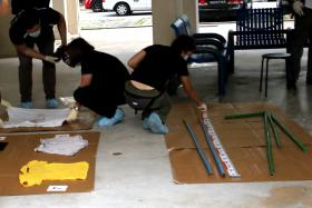 Police collecting evidence at the void deck of the block.