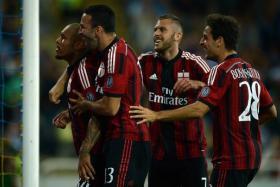 AC Milan's Dutch midfielder Nigel de Jong (L) celebrates with teammates after scoring during the Serie A football match Parma vs AC Milan at Parma's Ennio Tardini Stadium on September 14, 2014.