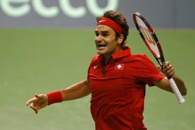 Roger Federer reacts after winning his Davis Cup semi-final tennis match against Italy's Fabio Fognini at the Palexpo in Geneva September 14, 2014.