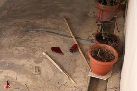 MESS: Debris at the front of Mr Koh's house, including the snapped wooden stick the woman had used to break the joss-stick holder.