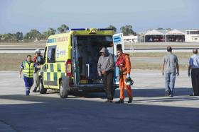 A migrant is helped by an Armed Forces of Malta airman to a waiting ambulance after being brought to Malta by helicopter.