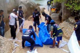 Thai workers carrying the bodies of two British tourists on Koh Tao island on Monday.