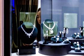 A vendor checking a display prior to the opening of the Hong Kong Jewellery and Gem fair.