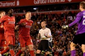 Liverpool players celebrate with Belgian goalkeeper Simon Mignolet (R) after their 14-13 penalty shoot out victory over Middlesbrough in the League Cup at Anfield.